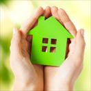 Mains tenant une maison verte